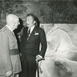 """El pintor Salvador Dalí entragando al jefe de Estado Francisco Franco el cuadro que pintó de la nieta mayor del Caudillo. Dalí dijo que representaba: """"en las nubes constantemente cambiantes de la diplomacia se recorta el caballo de la historia que deja ver el horizonte luminoso y el cielo inmutable de la España serena del Caudillo""""."""